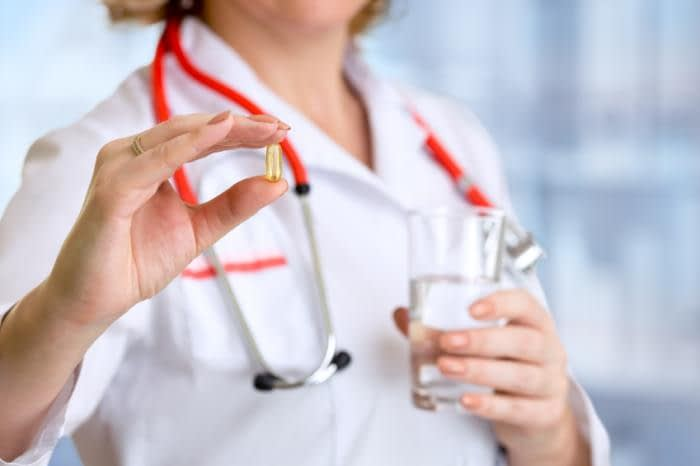 a doctor is holding a fish oil capsule and a glass of water 1